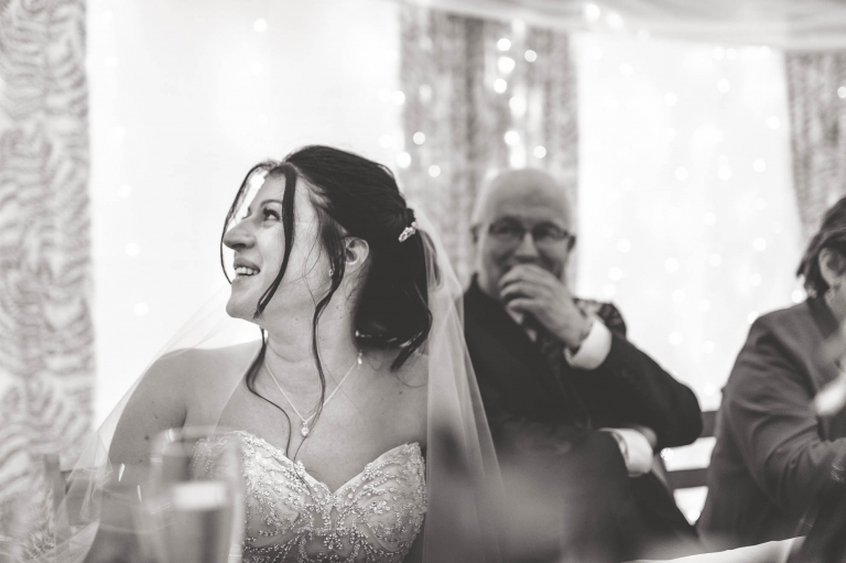 Bride smiles as the groom gives his speech