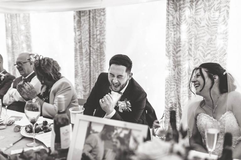 Bride and groom laugh at best mans joke
