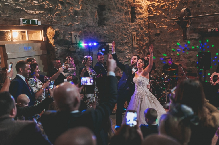 Bride and groom wave hands during first dance