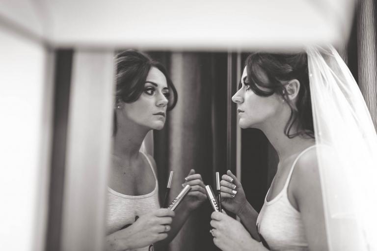 bride applies lipstick in mirror