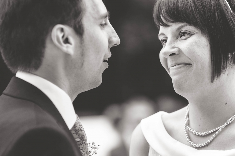 bride and groom smile at each other during the exchange of vows