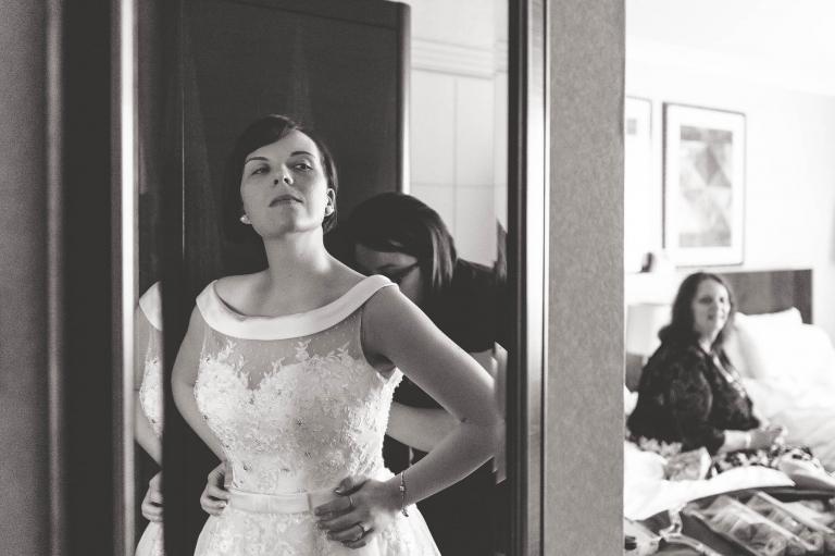 bride with her dress on looking in mirror