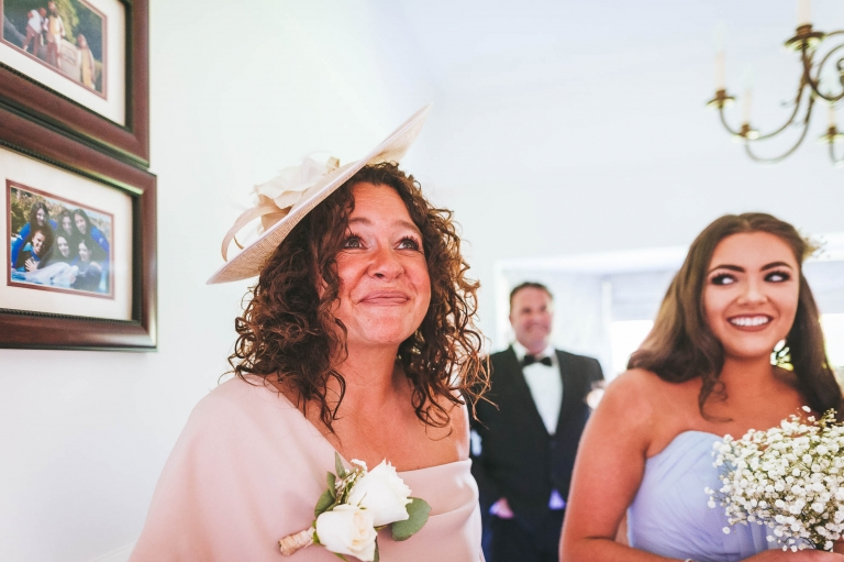 Mother of the bride smiles as she sees her daughter in her dress