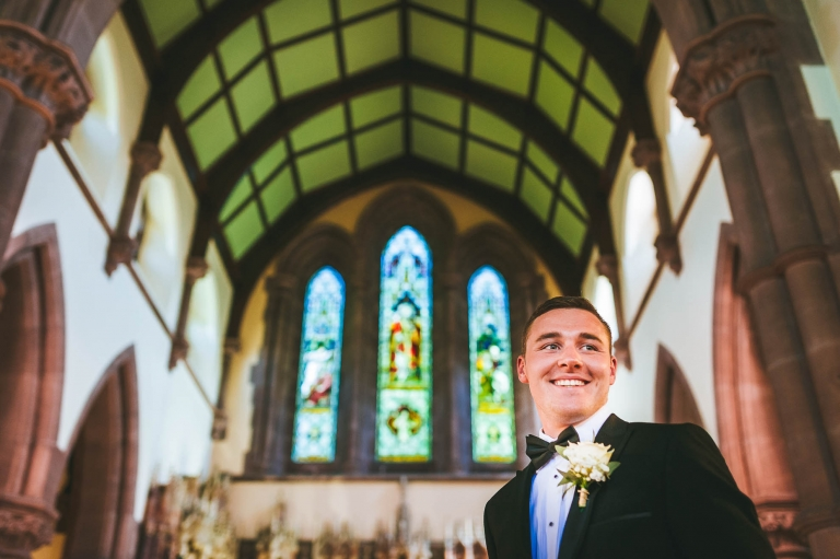 Groom smiles as he waits for his bride