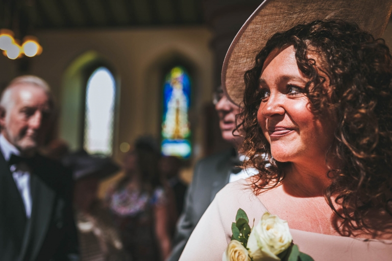 Mother of the bride watches her daughter walk up the aisle