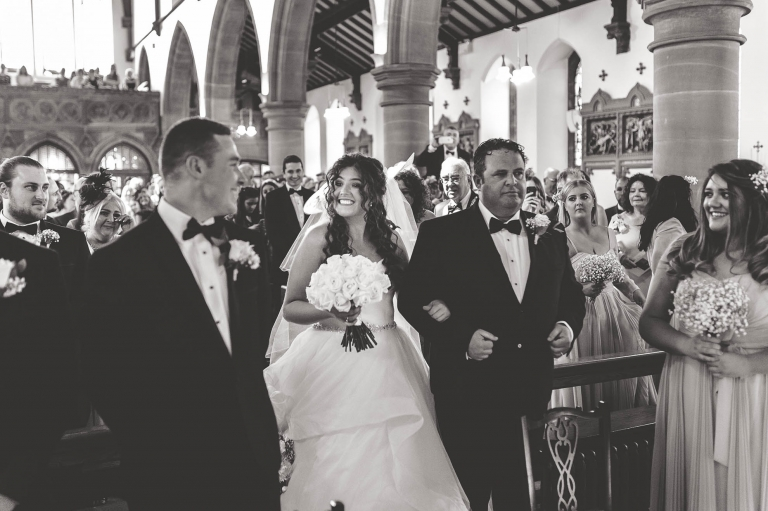 Bride and groom smile at each other as bride arrives at altar