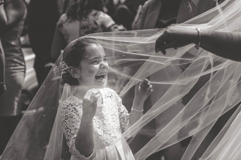 Flower girl plays under veil