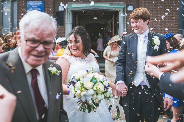 Guest throw confetti over newlyweds
