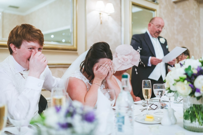 Bride hides face in hands during speeches