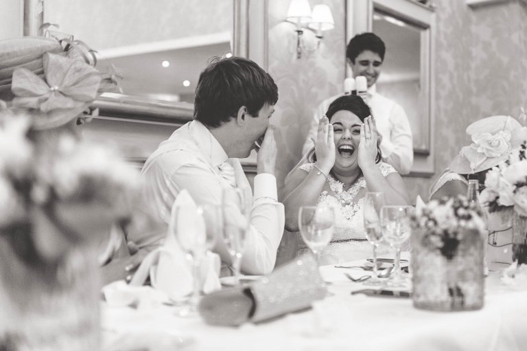 Bride and groom laugh at best mans speech