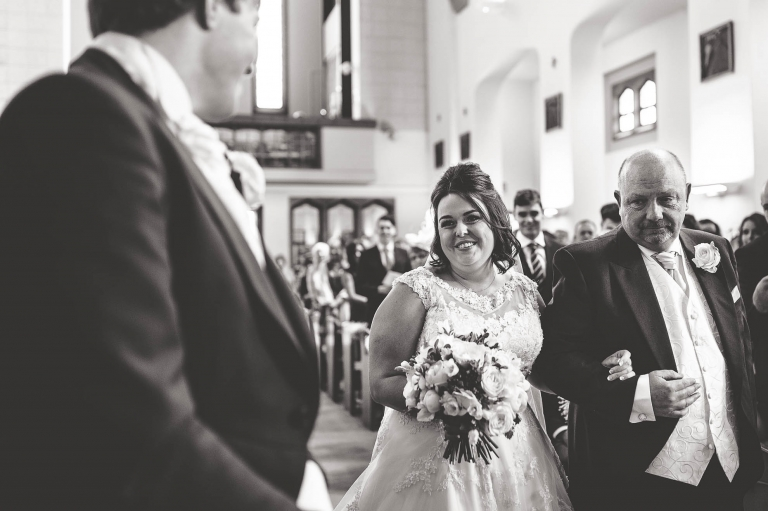 Bride and groom smile at each other as she arrives at the altar