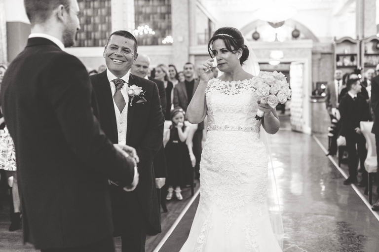 Bride sheds a tear as she walks up aisle
