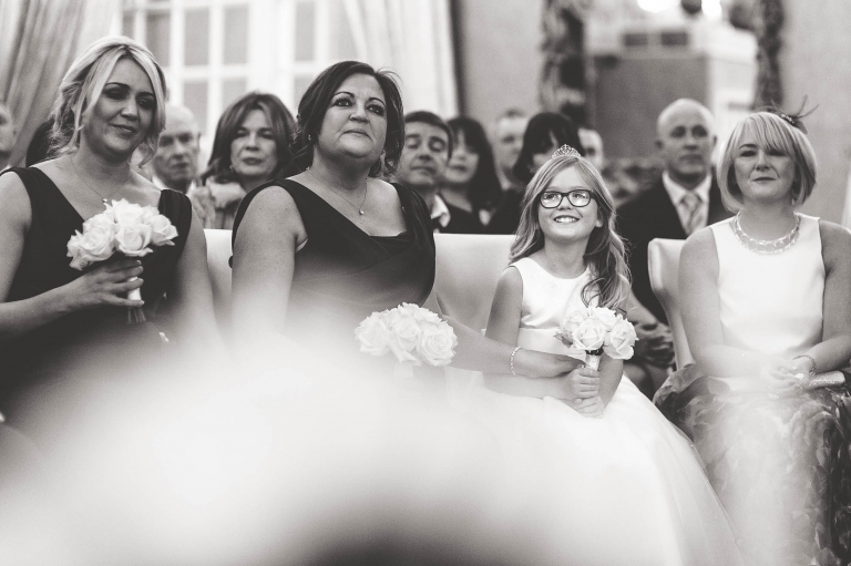 Bridesmaids and flower girl smiling during the exchange of rings