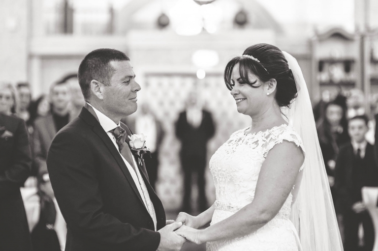 Bride and groom smile at each other during the vows