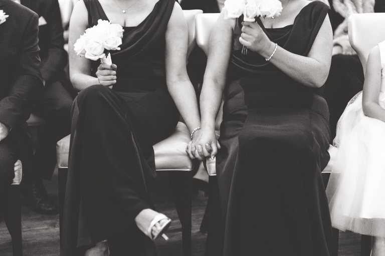 Bridesmaids holding hands during the ceremony