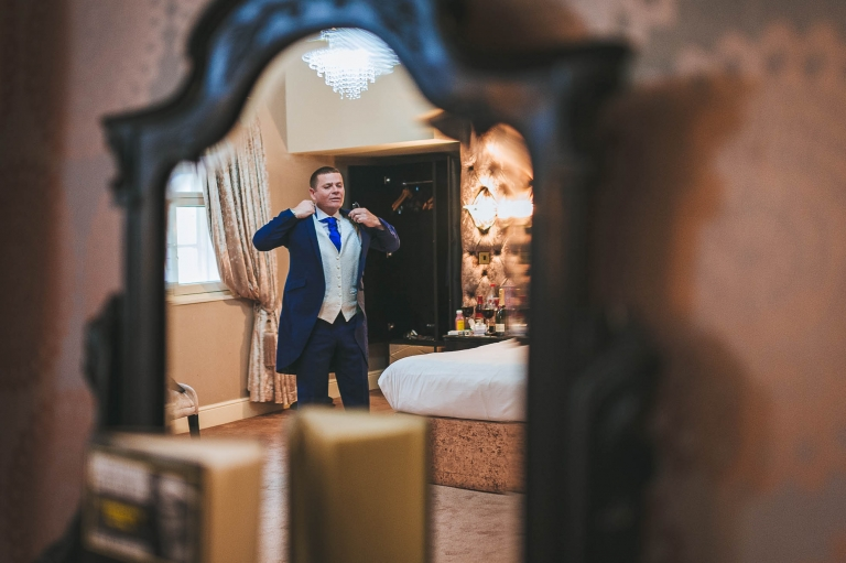 Groom getting ready reflection in mirror