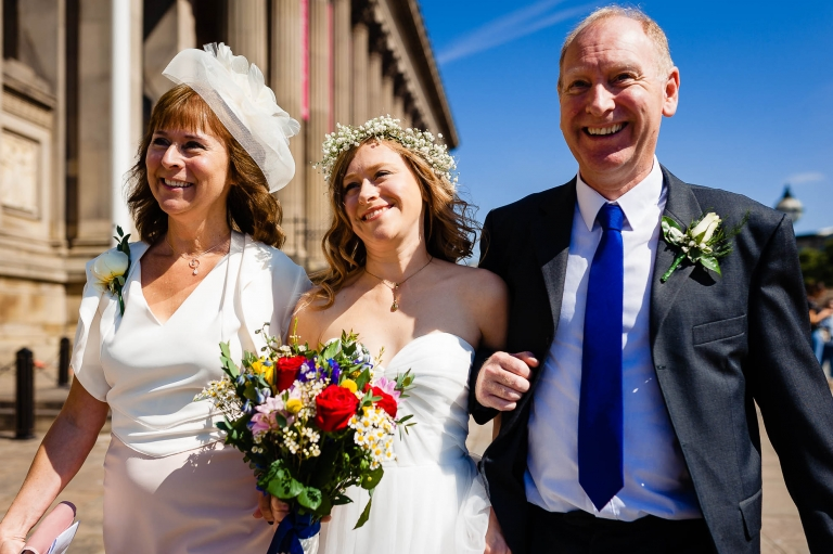 Bride and her mother & father walk to St Georges Hall