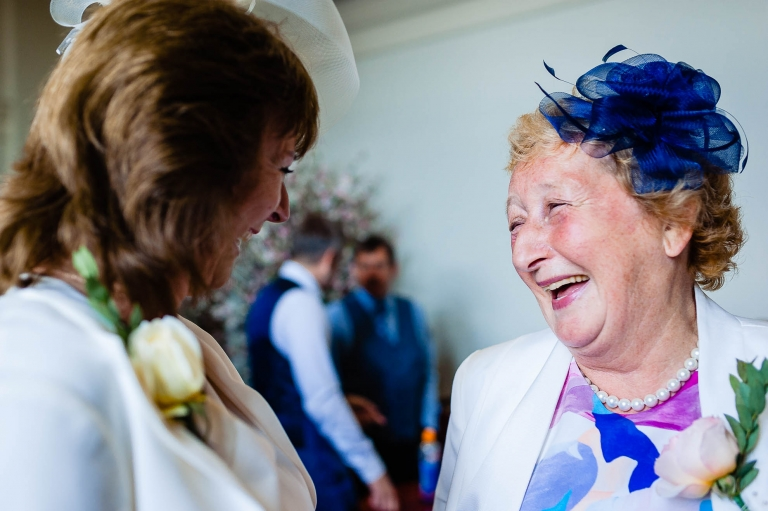 Mother of the groom and mother of the bride share a joke