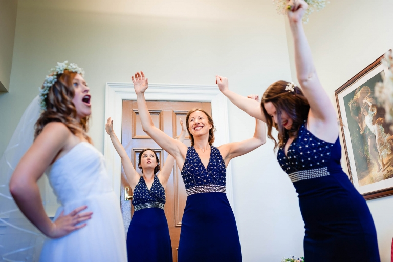 Bride and bridesmaids playing about before the ceremony