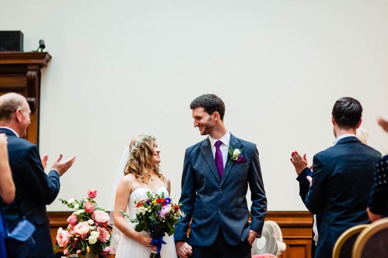 The newly weds smile at each other before they walk back down the aisle