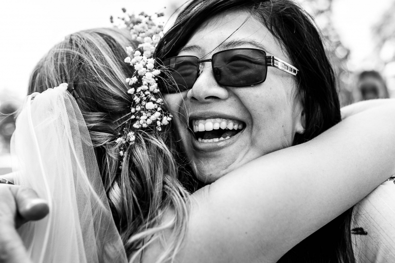 Wedding guest hugs bride at drinks reception
