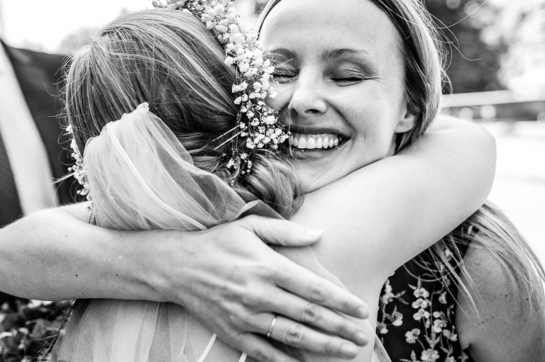 bride hugs guest during drinks reception