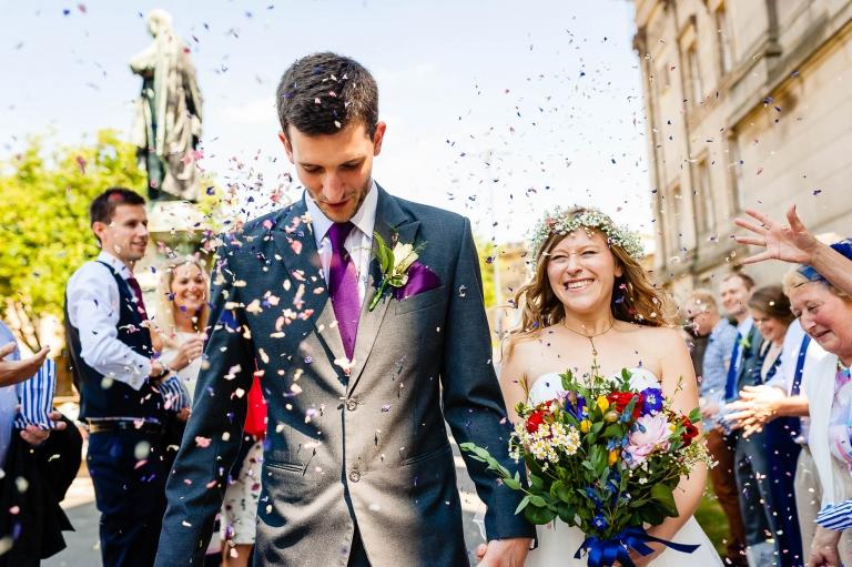 Bride and groom walk through the confetti throw