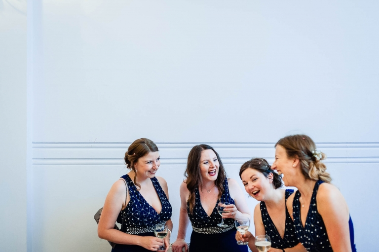 Bridesmaids share a joke during drinks reception