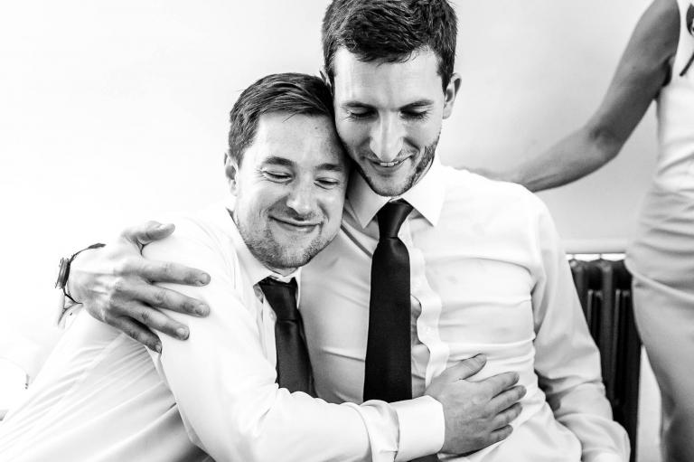 Best man and groom hug