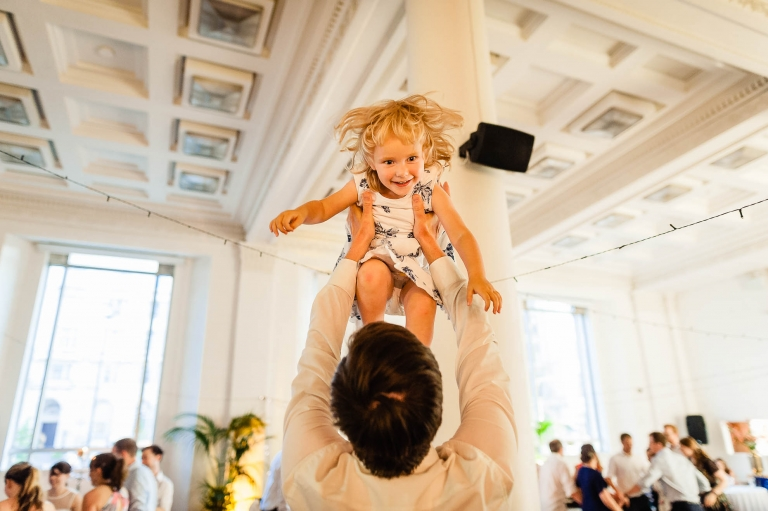 Little girl thrown up in the air during wedding reception