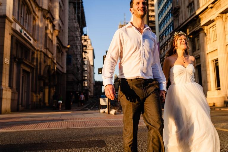 Happy couple walk towards the Three Graces