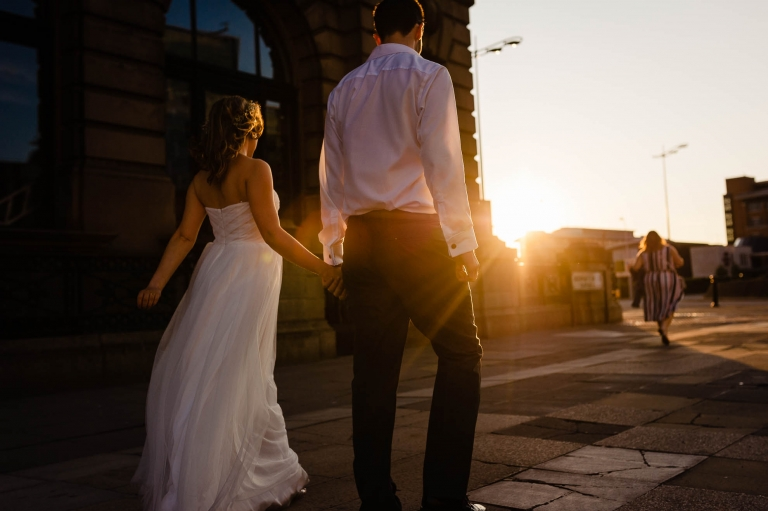 Bride and groom walk past the Liver building