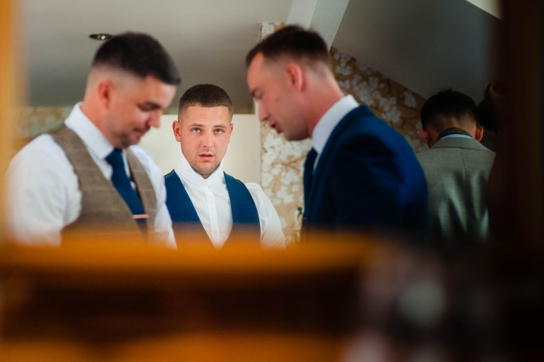 Groom looks in mirror as he gets dressed