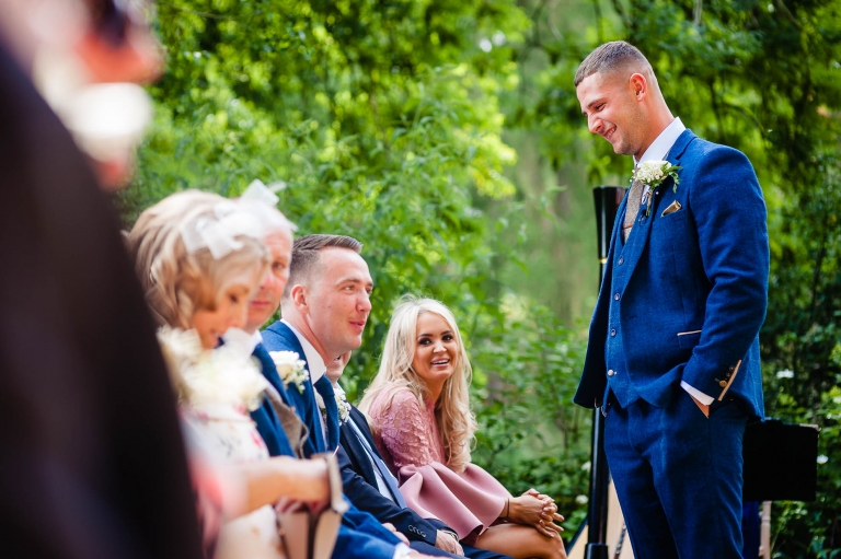 Groom shares a joke with his groomsmen before the wedding ceremony