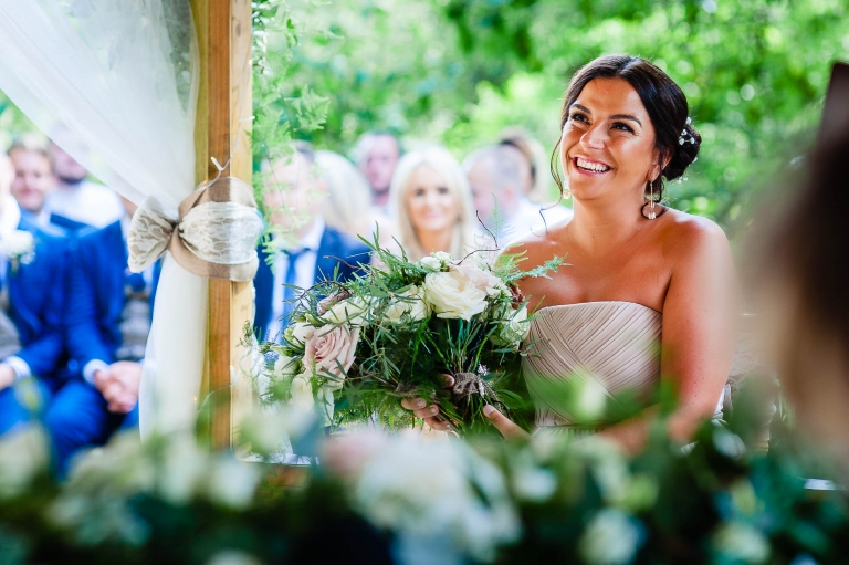 Bridesmaid smiles during wedding ceremony