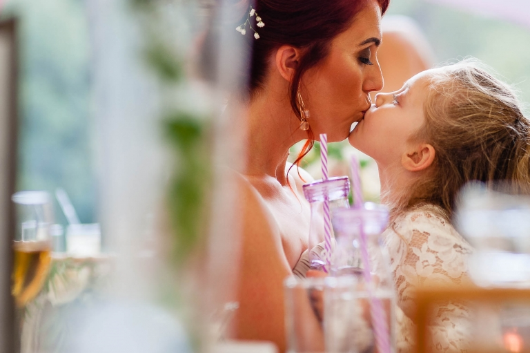 Mum and flower girl kiss during the speeches