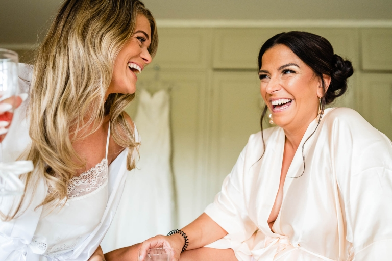 Bride and bridesmaid share a joke