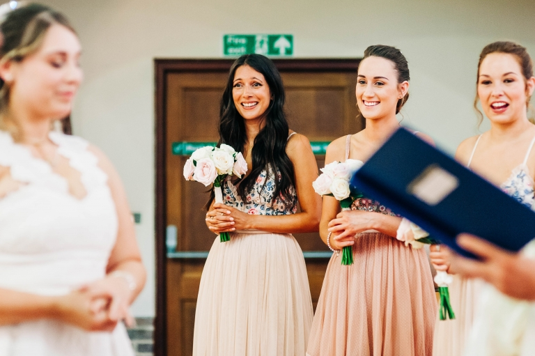 Bridesmaids smile during the ceremony