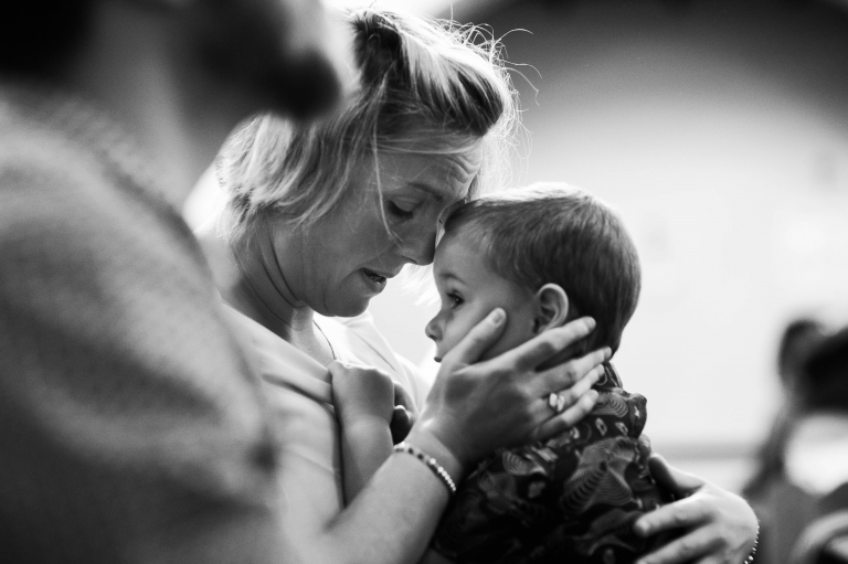 Wedding guest hugs her child
