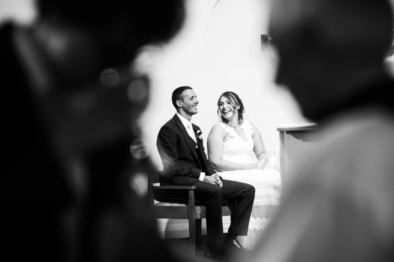 Bride and groom share a joke during communion