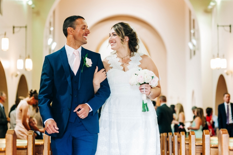 bride and groom smile at each other as they walk back down the aisle