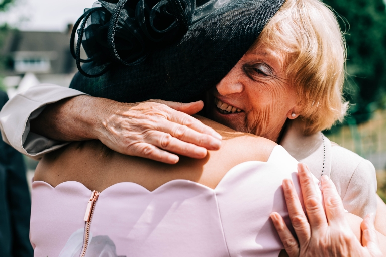Wedding guest hugs mother of the bride