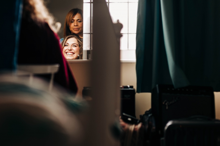 Bride laughs as she has her hair done