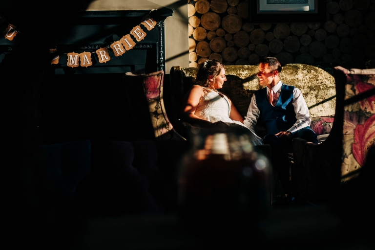 Bride and groom sitting on a chair in the sunlight