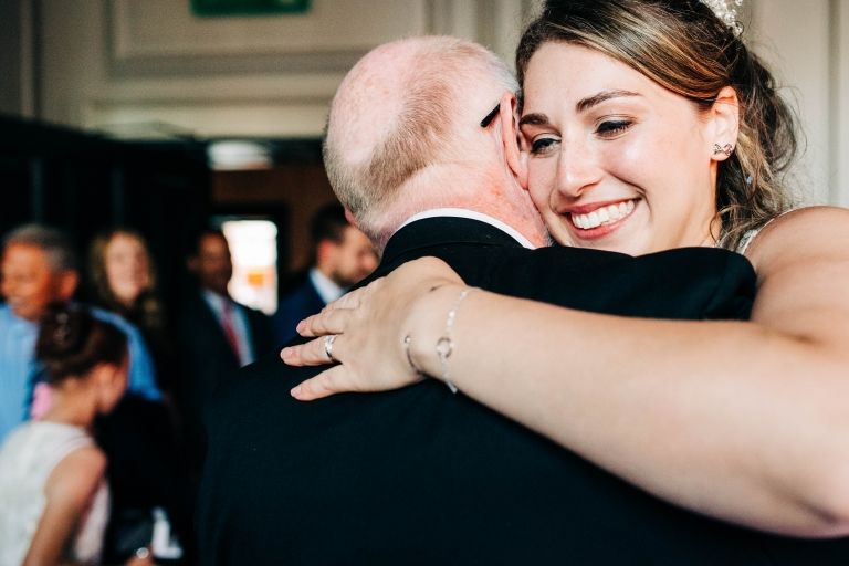 Bride smiles as she dances with her father