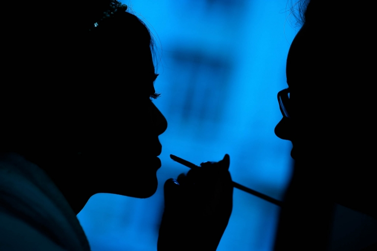 Silhouette of bride having make up applied