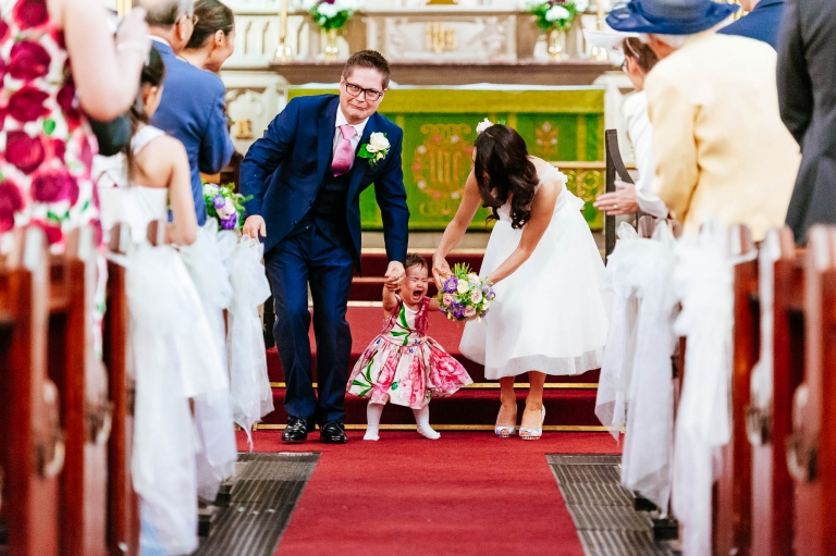 Bride and groom walk their tearful young daughter back down the aisle
