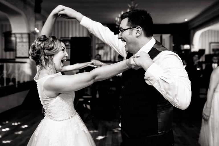 Bride and groom laughing dancing together
