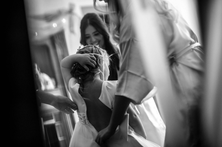 Flower girl is helped into her dress
