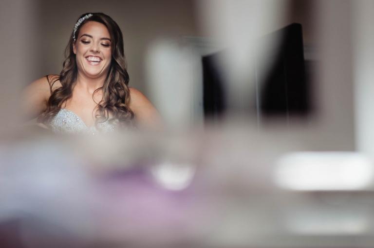 Bride laughing as bridesmaids adjust her dress